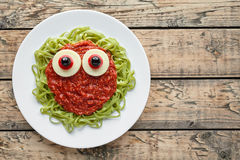 Green spaghetti pasta creative halloween food monster with fake blood tomato sauce Royalty Free Stock Photo