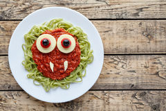 Green spaghetti pasta creative halloween food vampire monster with fake blood tomato sauce and big mozzarella eyeballs Royalty Free Stock Photos