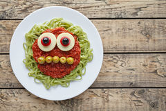 Green spaghetti pasta creative spooky halloween food monster with smile tomato sauce and funny big mozzarella eyeballs Royalty Free Stock Photo