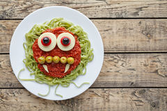 Green spaghetti pasta creative spooky halloween vegetarian food vampire monster with smile. Fake blood tomato sauce and funny big mozzarella eyeballs holiday Stock Photography