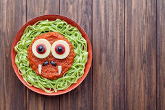 Green spaghetti pasta scary halloween food vampire monster with smile. Fake blood tomato sauce moustaches and funny big mozzarella eyeballs decoration kid Stock Image