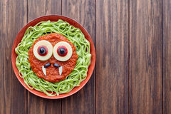 Green spaghetti pasta spooky halloween vegetarian food vampire monster. With smile, fake blood tomato sauce and funny big mozzarella eyeballs decoration kid Stock Images