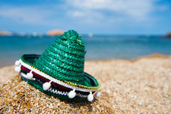 Green Spanish straw hat at beach. Green Spanish straw Sombrero in sand at the beach royalty free stock photography