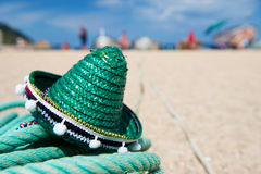 Green Spanish straw hat at beach. Green Spanish straw Sombrero in sand at the beach Stock Images
