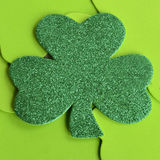 Green Sparkle Shamrock. Green sparkly shamrock laying on light green shamrocks royalty free stock photography