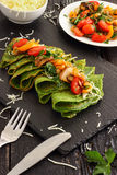 Green Spinach Crepes. Vegetarian meal with mushrooms, tomatoes, peppers and garlic Stock Image