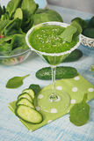 Green spinach and cucumber smoothie on light blue wooden backgro. Martini glass filled with fresh green spinach and cucumber smoothie on light blue wooden Royalty Free Stock Photo