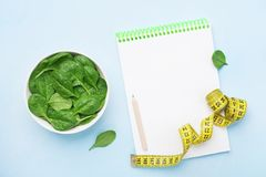 Green spinach leaves, notebook and tape measure on blue table top view. Diet and healthy food concept. stock image