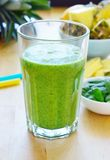 Green spinach and pineapple smoothie. On table. Fruit smoothie made with baby spinach leaves, pineapple, banana and pear Stock Photos