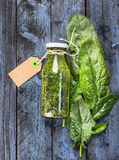 Green spinach smoothie bottle with sign  lies on blue wooden background Royalty Free Stock Images