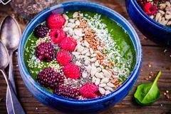 Green spinach smoothie bowl with raspberry,blackberry,flax seeds, sunflower seeds and coconut chips Stock Photography