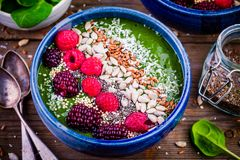 Green spinach smoothie bowl with raspberry,blackberry,flax seeds, sunflower seeds and coconut chips Royalty Free Stock Image