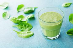 Green spinach smoothie in glass for healthy breakfast. Green spinach smoothie in glass for healthy breakfast on blue table stock photos
