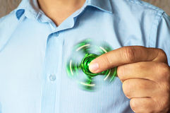 Green spinning spinner in the hand of a man Royalty Free Stock Images