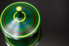 Green spinning top, macro, play, children, child play, toy Royalty Free Stock Images