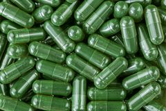 Green Spirulina powder, blue-green algae in clear capsules Stock Photos