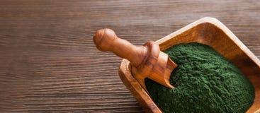 Green spirulina on wood background. Ground Spirulina on wood background royalty free stock image