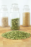 Green split peas. On a wooden board, with a jar of split peas and two jars of grains in the background Royalty Free Stock Photography