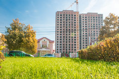 Green spring grassy lawn on blurred background of high-rise building and crane Stock Photo