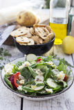 Green spring salad. On white wooden table with prencils and a lime Royalty Free Stock Photography