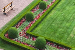 Green, square, manicured, garden and bench in Luxembourg City. Corner of a square, green, manicured formal garden. There is a border of colorful flowers within a royalty free stock photography