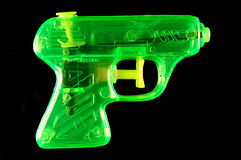 Green Squirt Gun. Toy squirt gun isolated on a black mirrored background royalty free stock image