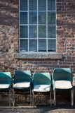 Green stacking chairs with brick background royalty free stock image