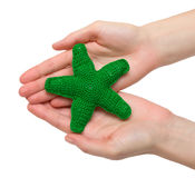 Green starfish. Hand made toy - green starfish in female hands. Isolation Royalty Free Stock Photo
