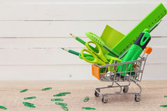 Green stationery objects in mini supermarket cart on the table. Stock Photos