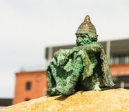 Green statue just chilling on rock. Looking over waterfront, beach Stock Photography