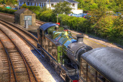 Green steam train engine and carriage on railway tracks in vivid colourful HDR Royalty Free Stock Photography