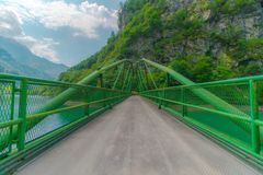 Green steel bridge in the middle of the mountains on the river in the woods royalty free stock images