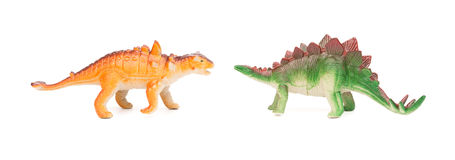 Green stegosaurus and orange pinacosaurus toy on white background Royalty Free Stock Photo