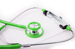 Green Stethoscope with plastic clipboard , blank paper Stock Photos