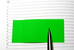 Green sticky note and pensil. On background Royalty Free Stock Photo