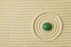 Green stone on surface of yellow sand Royalty Free Stock Photo