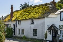 Green straw roof cottage at Porlock Weir, Somerset. View of medieval cottage built with  stone and with  straw roof with green grass on it, in historic touristic Royalty Free Stock Images