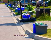 Green Street. Grey and blue recycling bins by the curb on a residential street Stock Images