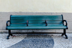 Green street bench on sidewalk Royalty Free Stock Images