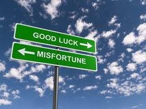 Good luck versus misfortune illustration. Green street sign with white text graphics good luck and misfortune with directional arrows against blue skies Stock Images