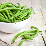 Green string beans in a bowl. On rustic wooden table Stock Photos