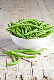 Green string beans in a bowl. On rustic wooden table Royalty Free Stock Images