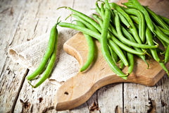 Green string beans. Closeup on wooden board Stock Images