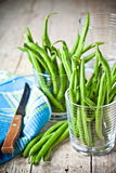 Green string beans in glasses. Napkin and knife closeup on rustic wooden background Stock Photography