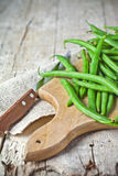 Green string beans and knife. Closeup on wooden board Royalty Free Stock Photography