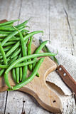 Green string beans and knife. Closeup on wooden board Stock Photo