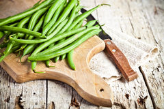 Green string beans and knife. Closeup on wooden board Stock Photos