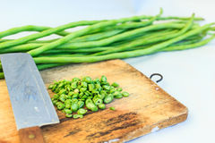 Green string beans and knife. Closeup on wooden board Royalty Free Stock Images