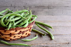 Raw green beans in a brown wicker basket and on an old wooden background. Raw diet food. Vegan food. Green string beans. Raw green string beans. Fresh green royalty free stock images