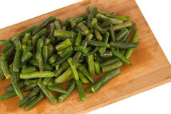 Green string beans on a wooden board. On a white background Royalty Free Stock Images